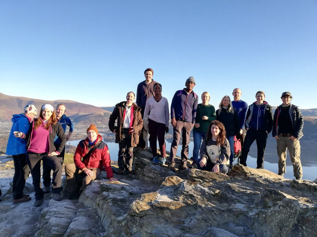 Photo of 14 people smiling at the top of one of the peaks.