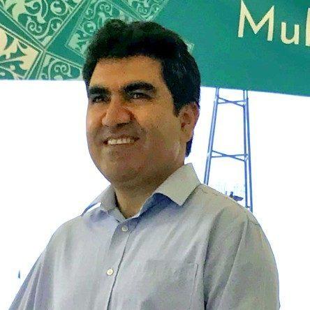 Photo of Adil smiling.