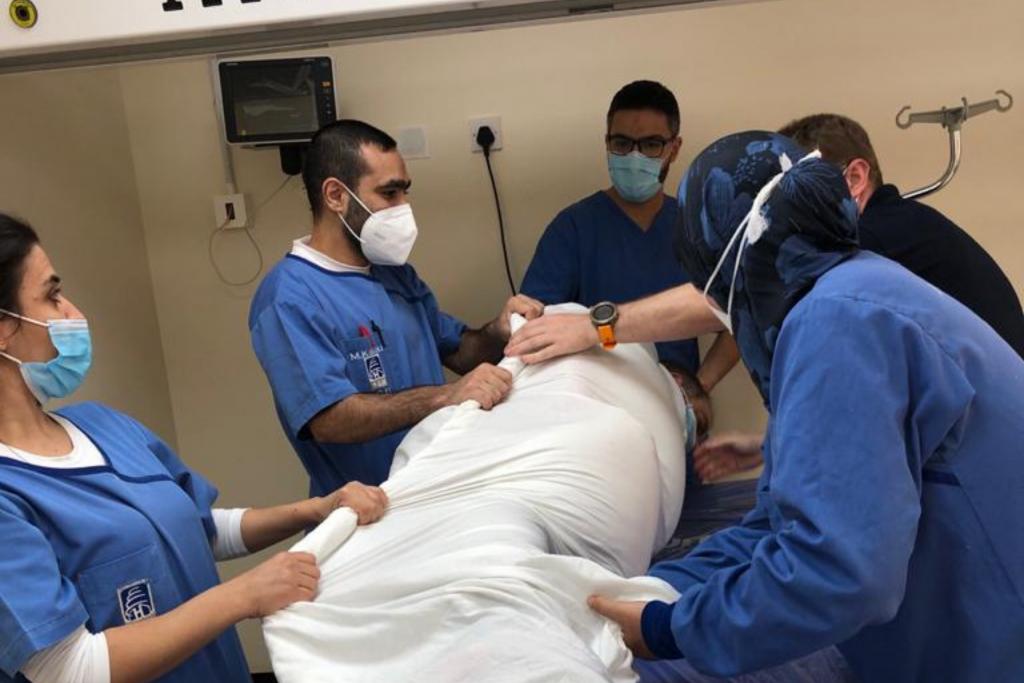 UK EMT team deliver training in proning a patient (D Ritzau-Reid, Lebanon 2020).