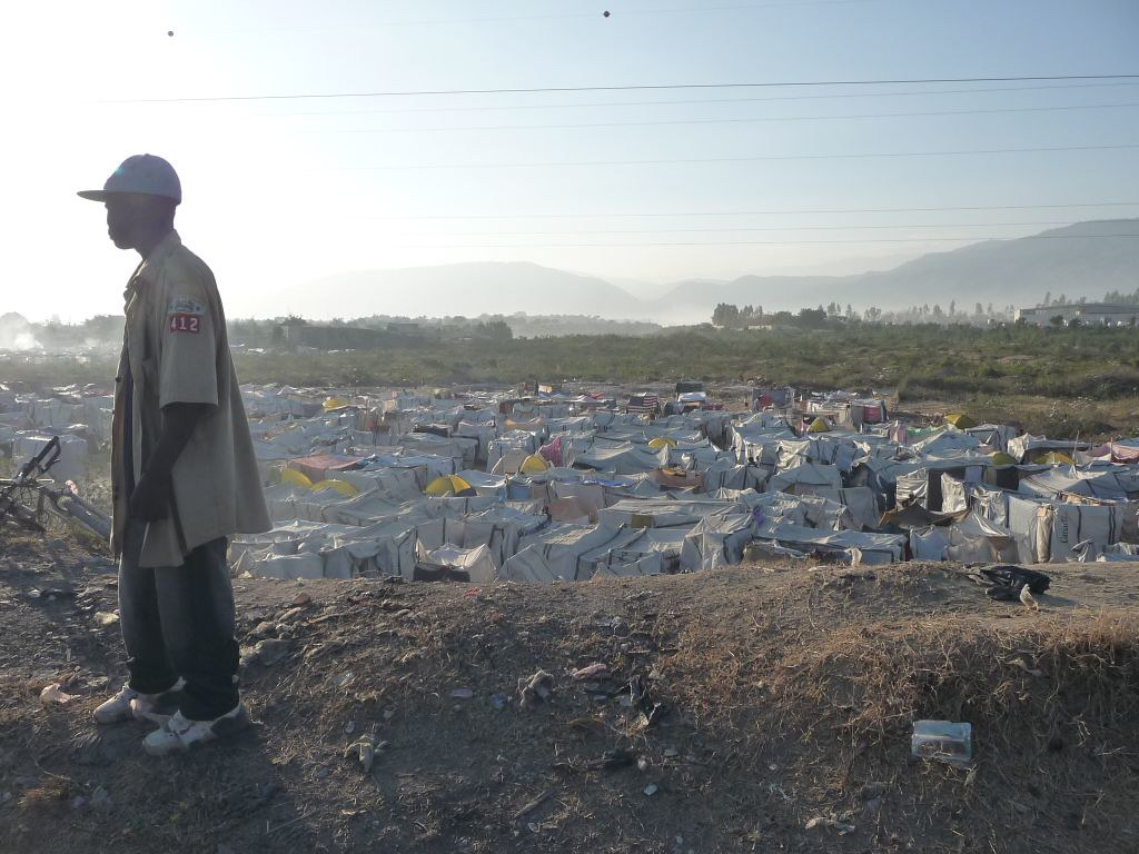 A man overlooking a tent village in Haiti.